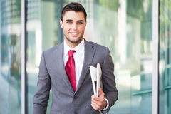 Businessman holding a newspaper under his arm Royalty Free Stock Images