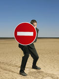 Businessman Holding 'No Entry' Sign In Desert royalty free stock image