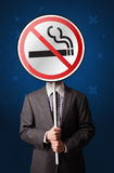 Businessman holding no smoking sign. Smart businessman holding round sign with no smoking graphic royalty free stock photos