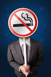 Businessman holding no smoking sign. Smart businessman holding round sign with no smoking graphic royalty free stock photo