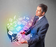Businessman holding notebook with colorful hand drawn multimedia Royalty Free Stock Photos