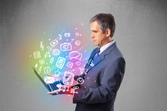 Businessman holding notebook with colorful hand drawn multimedia Royalty Free Stock Images