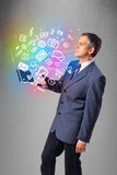 Businessman holding notebook with colorful hand drawn multimedia Royalty Free Stock Photography