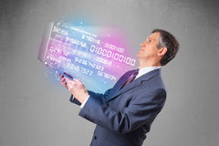 Businessman holding notebook with exploding data and numbers Royalty Free Stock Photo