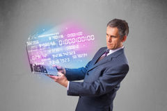 Businessman holding notebook with exploding data and numbers. Attractive businessman holding notebook with exploding data and numbers Stock Photo