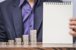 Businessman holding notebook and growing money coin Royalty Free Stock Images