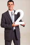 Businessman holding number Stock Photo