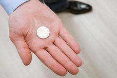 Businessman holding one coin Royalty Free Stock Images