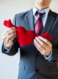 Businessman holding open armed heart with hands - warm welcome a Stock Photography