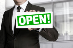 Businessman holding open sign to viewer Royalty Free Stock Image