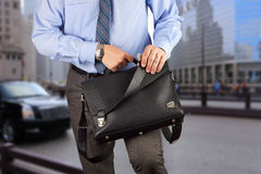 Businessman holding and opening  a  leather briefcase Royalty Free Stock Photo