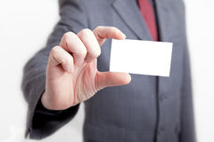 Businessman holding out a blank card Stock Image
