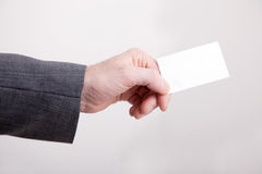 Businessman holding out a blank card Royalty Free Stock Images