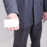 Businessman holding out a blank card Stock Photography