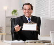 Businessman holding out clipboard stock image