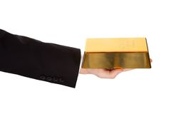 Businessman holding out a gold bar. Cropped view of the arm of a businessman holding out a gold bar in a depiction of success and wealth isolated on white royalty free stock image