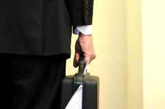 Businessman holding overloaded briefcase Royalty Free Stock Image