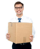 Businessman holding packed carton Stock Photography