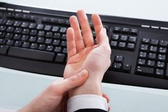 Businessman Holding Painful Wrist At Office Desk Royalty Free Stock Photos