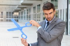 Businessman holding a pair of scissors Royalty Free Stock Photography