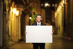 Businessman holding a panel in a city street Royalty Free Stock Photos