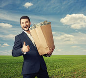 Businessman holding paper bag with money Royalty Free Stock Images