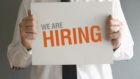 Businessman holding paper board with WE ARE HIRING title.