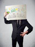 Businessman holding a paper with charts and cityscape in front o Royalty Free Stock Photos