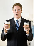 Businessman holding paper coffee cups Stock Photo