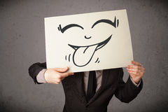 Businessman holding a paper with funny smiley face in front of h Royalty Free Stock Photography