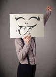 Businessman holding a paper with funny smiley face in front of h Stock Photography