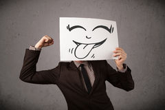 Businessman holding a paper with funny smiley face in front of h Stock Photo