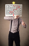 Businessman holding a paper with a labyrinth on it in front of h Stock Photos