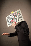 Businessman holding a paper with a labyrinth on it in front of h Stock Images