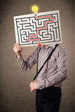 Businessman holding a paper with a labyrinth on it in front of h Royalty Free Stock Images