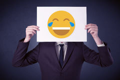 Businessman holding paper with laughing emoticon Stock Image
