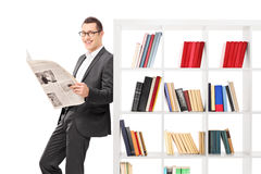 Businessman holding a paper and leaning on bookshelf Stock Photography