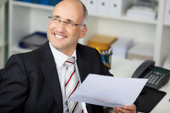 Businessman Holding Paper While Looking Away At Desk Royalty Free Stock Image