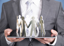 Businessman holding paper people on tablet Royalty Free Stock Images