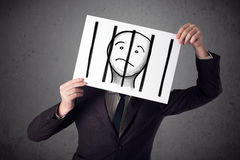 Businessman holding a paper with a prisoner behind the bars on i Royalty Free Stock Photos
