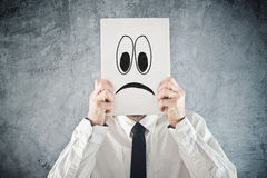 Businessman holding paper with sad face in front of his head stock image