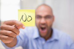 Businessman holding paper that says NO. Frustrated young businessman holding paper that says NO stock photography