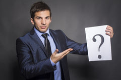 Businessman holding paper show question mark Stock Photo