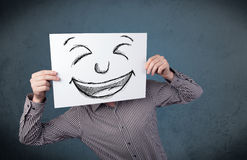 Businessman holding a paper with smiley face in front of his hea Royalty Free Stock Image