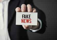 Businessman holding paper with text Fake News. Stock Photography