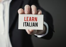 Businessman holding paper with text Learn Italian. Stock Image