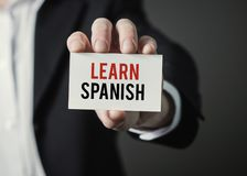Businessman holding paper with text Learn Spanish. Stock Photos