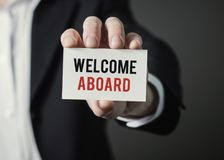 Businessman holding paper with text Welcome Aboard. Businessman holding card. Royalty Free Stock Photos