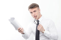 Businessman holding papers and biting glasses Stock Photography
