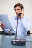 Businessman holding paperwork while on the phone Royalty Free Stock Images